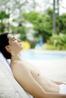 A bare-chested man relaxing beside a swimming pool