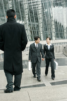 A couple in business suit walking together holding hands