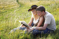 A couple sitting on the grass reading book