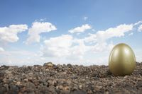 A golden egg placed on top of soil, against clear sky