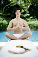 A guy doing yoga by the poolside