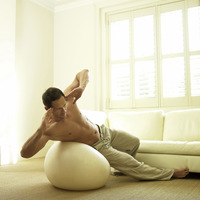 A man doing side sit ups with fitness ball