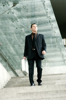 A man in business suit carrying a briefcase walking down the stairs