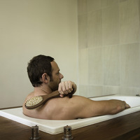 A man scrubbing his back in the bathtub