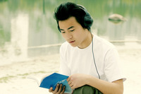 A man sitting on the lakeside listening to music on his headphone while reading book