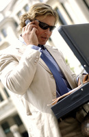 A man with sunglass searching for documents from his briefcase while talking on the hand phone