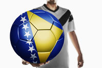 A soccer player holding bosnia and herzegovina soccer ball