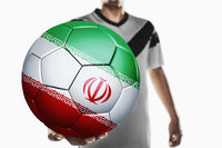 A soccer player holding iran soccer ball
