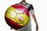 A soccer player holding spain soccer ball