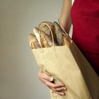 A woman holding a bag of breads