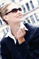 A woman in business suit and sunglasses holding a pen