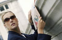 A woman in business suit and sunglasses reading a newspaper