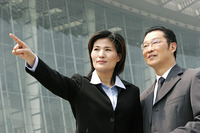 A woman in business suit showing something to a bespectacled man