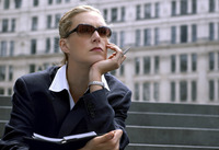 A woman in formal wear and sunglasses sitting on the bench holding a pen and a planner