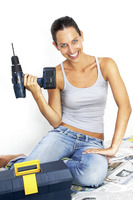 A woman in jeans sitting on the floor holding a driller
