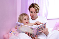 A woman sitting on the bed reading bedtime story for her daughter