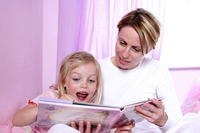 A woman sitting on the bed reading bedtime story for her excited daughter