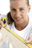 A woman using a measuring tape to measure a wood
