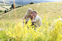 A woman whispering a little something to her boyfriend on the prairie