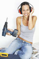 A woman with headphone sitting on the floor holding a driller