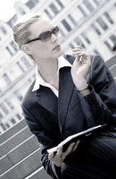 A woman with sunglass sitting on the stairs holding a pen and an organizer