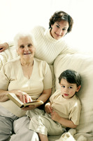 A young boy sitting with his grandmother and mother on the couch looking at the camera