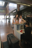 Airline check-in attendant checking passports of man and woman at the airport check-in counter