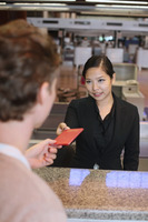 Airline check-in attendant returning man's passport at the airport check-in counter