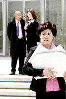 An angry looking woman holding a briefcase of papers