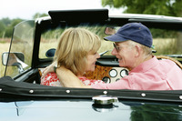An old couple sitting in a roofless car