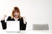 An overjoyed businesswoman after reading the good news on her laptop