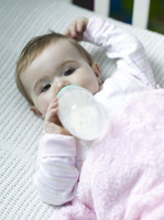 Baby girl lying on the crib drinking milk