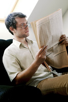 Bespectacled man reading newspaper