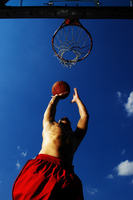 Bottom view of a man trying to shoot a ball into the hoop