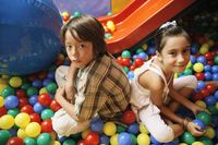 Boy and girl sitting in ball pool