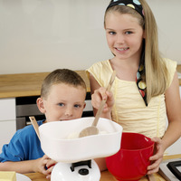 Boy and girl smiling at the camera while baking in the kitchen