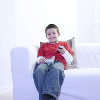 Boy holding a bowl of candies while watching television