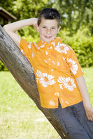 Boy leaning against a tree posing for the camera