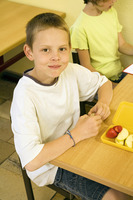 Boy looking at the camera with his lunch box on the table