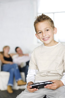 Boy playing with portable video game, his parents in the background