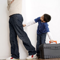 Boy pulling his father's jeans while trying to carry toolbox