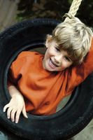Boy pushing his head out through a tyre hole