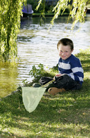 Boy sitting by the river holding fishing net