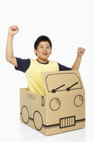 Boy sitting in a cardboard bus, cheering