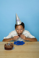 Boy with party hat eating cake