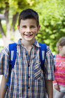 Boy with school bag smiling at the camera