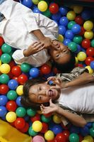 Boys in ball pool, making funny faces