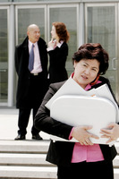 Business woman talking on the hand phone while carrying a briefcase of documents