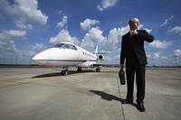 Businessman adjusting his tie on runway with private jet in the background