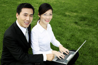 Businessman and businesswoman smiling at the camera while sharing a laptop